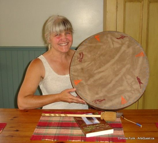 Noreen Kruzich holding a Native drum with totemic signatures of Algonkin and Nipissing chiefs.